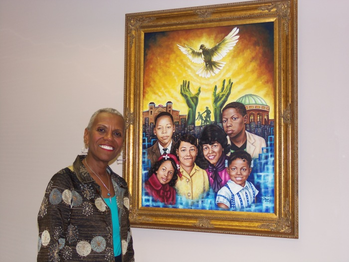 BCRI CEO Andrea Taylor smiles beside a painting in her office.